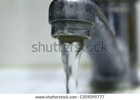 Bathroom faucet. Water flows from the tap. Close-up. Background. #1309099777