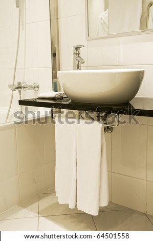 Bathroom fixtures with white washstand and faucet with towels