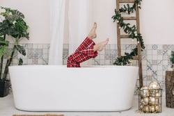 Bathroom. From the white bathtub, only a woman's legs in red check trousers are visible. Nearby is a vase with Christmas balls. Balinese style bathtub. New Year's bathroom. Christmas bustle