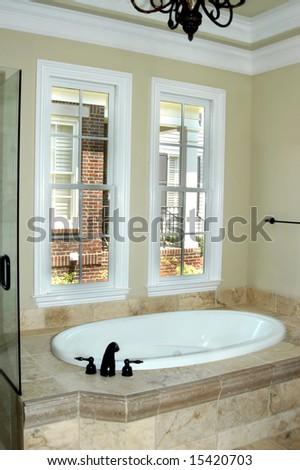 Bathroom has beautiful granite framed tub.  Double windows give lots of light to ornate bathroom.