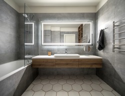 Bathroom in a modern style with gray and white tiles. There is a large mirror with luminous lamps, tabletop with wooden drawers and sink, bath with shower and glass partition, towel rack and a hanger.