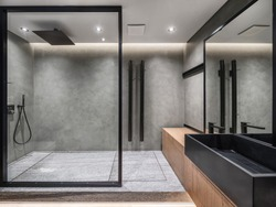 Bathroom in a modern style with gray tiled walls. There is a shower with a glass partition, wooden stand with a black sink and a faucet, large mirror, luminous lamps. Horizontal.