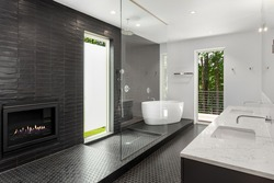 Bathroom in luxury home with large walk-in shower, double vanity, sinks, and tile floor. Also shows large soaking bathtub