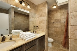 Bathroom in upscale home with marble vanity and skylight