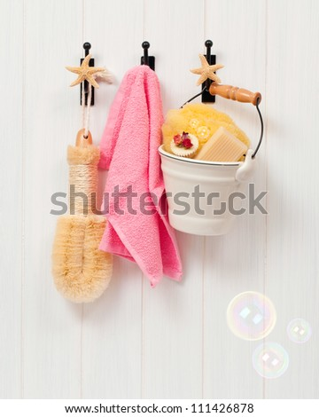 Bathroom products hanging on hooks on the bathroom door with soap bubbles