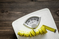 Bathroom scale and measuring tape on wooden background top view copyspace
