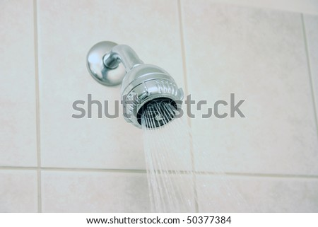 Bathroom shower head spraying water.