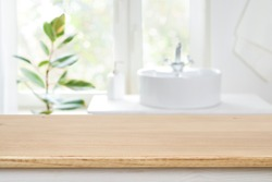 Bathroom sink near window with wooden table in front focus