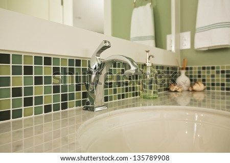 Bathroom Sink Of An Upscale Home/Horizontal Shot Of An Elegant, Polished And Clean Sink In An Upscale Home With Colorful Green Tiling