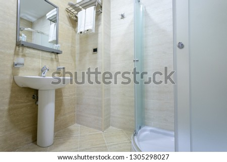 Bathroom,tiles and bright colors of broom, shower with frosted doors,mirror above the sink. Hanging a towel over the toilet on a hanger. #1305298027