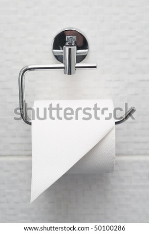 Bathroom tissue hanging on the wall. Toilet paper on white tiles