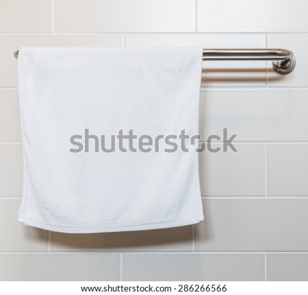 Bathroom Towel - white towel on a hanger prepared to use