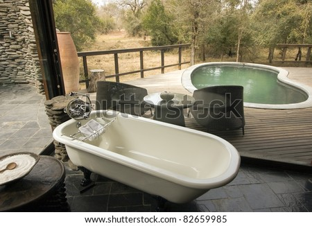 Bathroom view overlooking a pool and wooden deck at a lodge in Africa