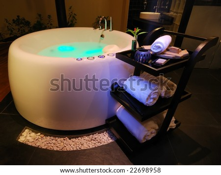 Stock photo bathroom with a modern jacuzzi whirlpool and towel trolley illuminated with different source of 22698958