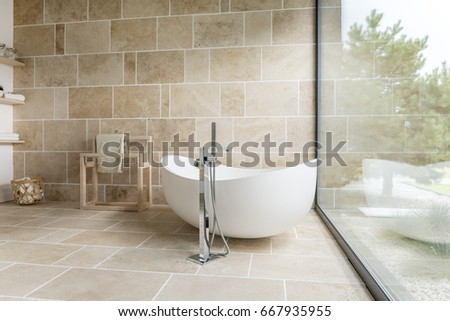 Shutterstock Bathroom with big window and wooden accesorises