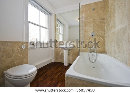 Bathroom With Light Brown Marble Tiles And Wooden Floor Stock