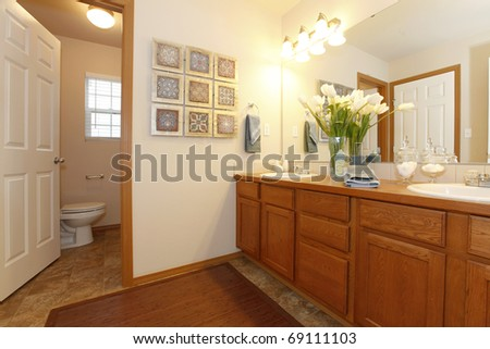 Bathroom with light walls and wood cabinet