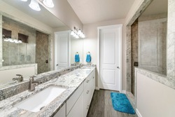 Bathroom with long vanity with two sinks and walk-in shower with half wall and glass. There is a mirror wall above the tile counter with towel hanging on side and vinyl wooden flooring with blue rug.