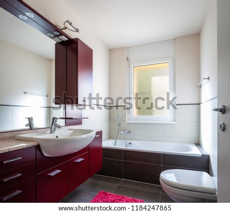 Bathroom with red wardrobe, bathtub and window. Nobody inside
