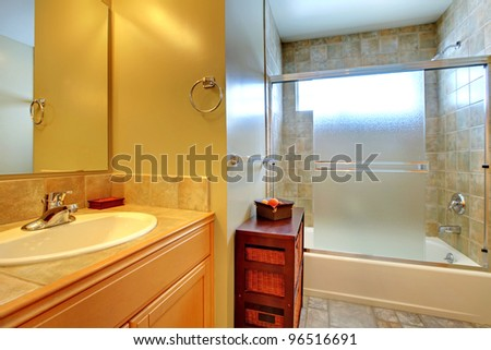 Bathroom with tub behind modern glass, stone tile, and white sink in a wood cabinet.