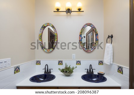 Bathroom with vanity with double sink, tiles ornamented with counter top with black sinks and oval shaped mirrors