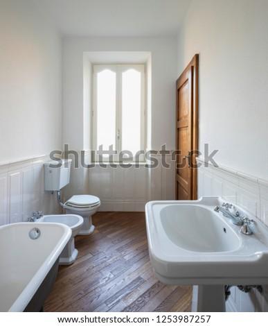 Bathroom with white walls and large black bathtub. Nobody inside.