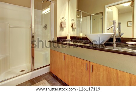 Bathroom with wood modern cabinets, glass shower and white sink.