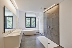 Bathtub in corian, Faucet and shower in tiled bathroom with windows towards garden
