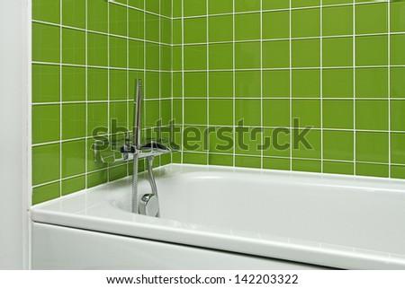 Bathtub with modern faucet in green bathroom