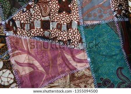 Batik material background, Indonesian material pieced together with white zigzag stiches in crazy quilt design in colorful blue green pink and brown colors #1355094500