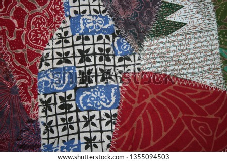 Batik material background, Indonesian material pieced together with white zigzag stiches in crazy quilt design in colorful blue green pink and brown colors #1355094503