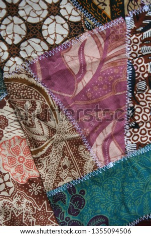 Batik material background, Indonesian material pieced together with white zigzag stiches in crazy quilt design in colorful blue green pink and brown colors #1355094506
