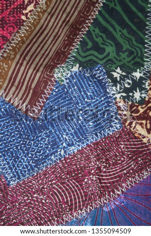 Batik material background, Indonesian material pieced together with white zigzag stiches in crazy quilt design in colorful blue green pink and brown colors #1355094509