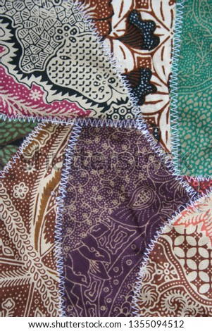 Batik material background, Indonesian material pieced together with white zigzag stiches in crazy quilt design in colorful blue green pink and brown colors #1355094512