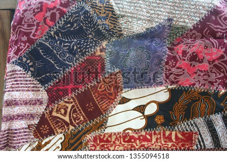 Batik material background, Indonesian material pieced together with white zigzag stiches in crazy quilt design in colorful blue green pink and brown colors #1355094518