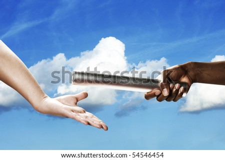 Baton handoff with white clouds and blue sky in background. Horizontal shot. - stock photo