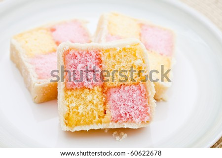 Battenberg cake on a white plate. Shallow DOF
