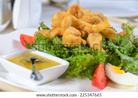 Battered deep fried calamari on a bed of fresh leafy green lettuce with a savory sauce served as a delicious seafood appetizer or meal
