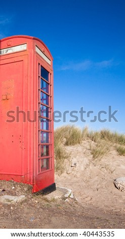 Battered English telephone box situated in the dunes of beach