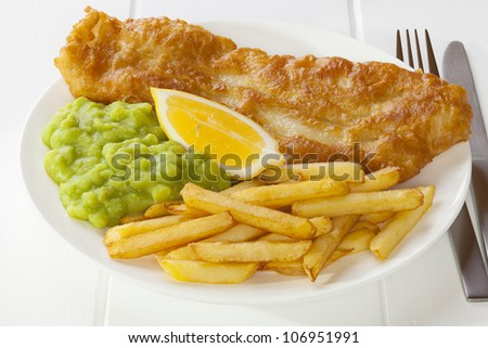 Battered fish served with chips and mushy peas