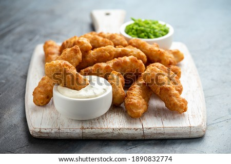 Battered Haddock fish, mini fingers with mashed peas, tartar sauce on white wooden board ストックフォト ©