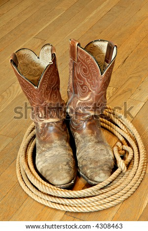 Battered old cowboy boots and lariat on hardwood floor.