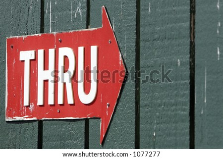 Battered Red Arrow with the word 'THRU' in White Letters (shallow focus).