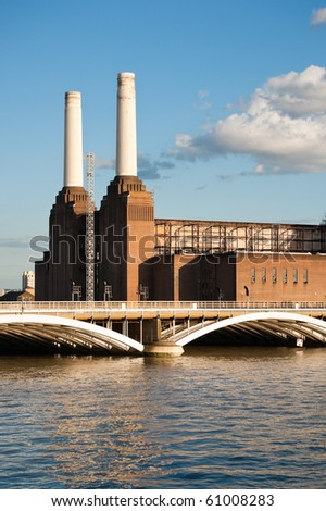 Battersea power station and bridge over the river Thames with reflection, against blue sky with white clouds