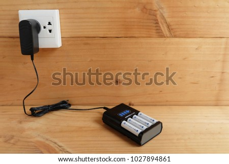 Battery Charger with battery size AA rechargeable with Charger Plug in power outlet adapter on wooden table #1027894861