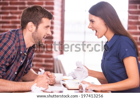 Battle of the sexes. Side view image of angry man and woman sitting face to face at the office table and shouting at each other