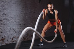 Battle ropes session. Attractive young fit and toned sportswoman training in gym
