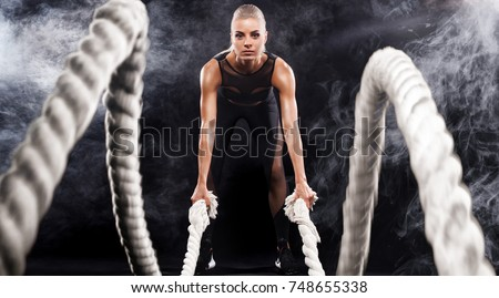 Battle ropes session. Attractive young fit and toned sportswoman working out in functional training gym doing exercise with battle ropes. Fitness and workout motivation #748655338