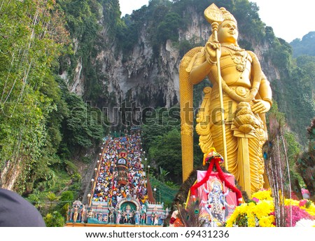 BATU CAVE, MALAYSIA - JAN 20 : Photo of lord murugan statue standing tall in front the cave entrance taken during Thaipusam on January 20, 2011 at Batu Cave temple, Malaysia .
