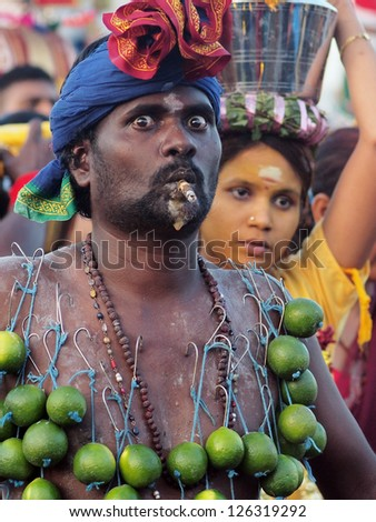 BATU CAVES, MALAYSIA - JANUARY 27: A devotee with limes hooked on his skin smokes a ceremonial cigar during the celebration of Thaipusam in Batu Caves, Malaysia on January 27, 2013.